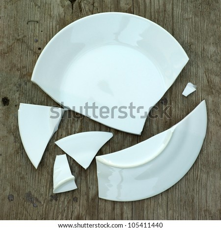 shards of a broken plate on a wooden surface - stock photo