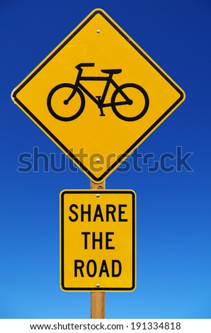 share the road with bicycles road sign isolated with blue sky background - stock photo