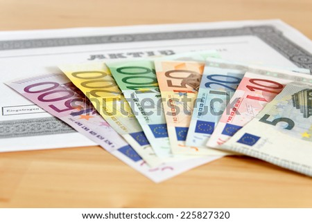 Share with fanned out Euro banknotes and depth of focus - stock photo