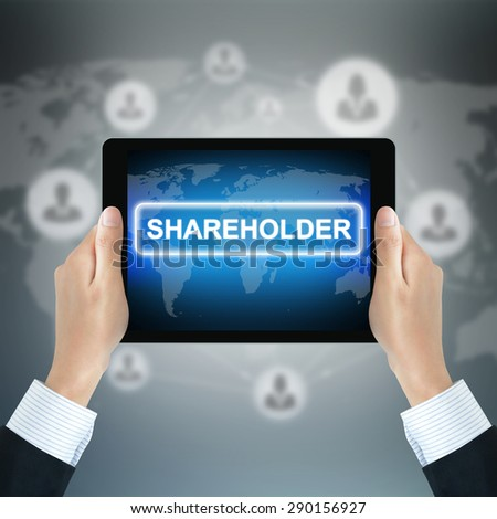 SHAREHOLDER word on tablet pc screen held by businessman hands