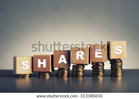 shares text written on wooden block with stacked coins on grey background - stock photo