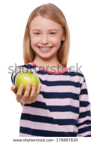 Sharing apple with you. Cheerful little girl stretching out hand with green apple while standing isolated on white - stock photo
