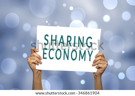 SHARING ECONOMY card in hand with abstract light background. Selective focus. - stock photo