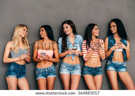 Sharing fresh news. Group of beautiful women holding mobile phones in their hands and smiling while standing against grey background