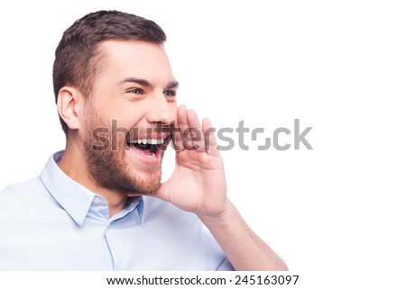 Sharing good news! Cheerful young man in formalwear holding hand near mouth and shouting while standing against white background