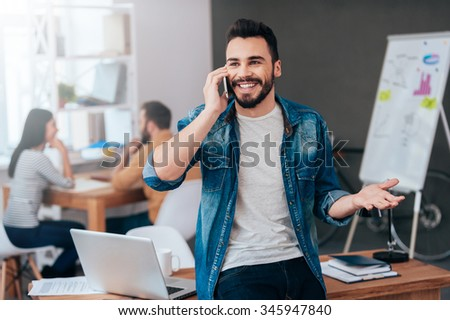 Sharing good news. Confident young smiling man talking on the mobile phone and gesturing while his colleagues working in the background - stock photo