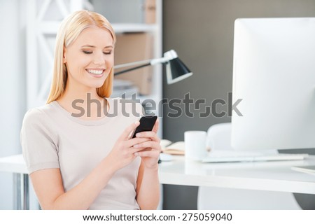 Sharing good news from colleagues. Beautiful young woman holding mobile phone and smiling while sitting near her working place in office - stock photo