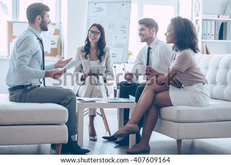 Sharing good news. Young handsome man gesturing and discussing something with his coworkers with smile while sitting on the couch at office  - stock photo