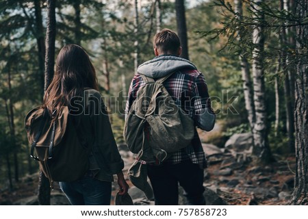 Sharing love to nature. Rear view of young couple hiking together in the woods while enjoying their travel