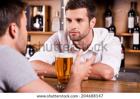 Sharing news with bartender. Rear view of male customer talking to bartender while sitting at the bar counter