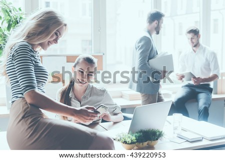Sharing the latest news. Two beautiful young businesswomen discussing something and smiling while sitting in office with colleagues standing in the background