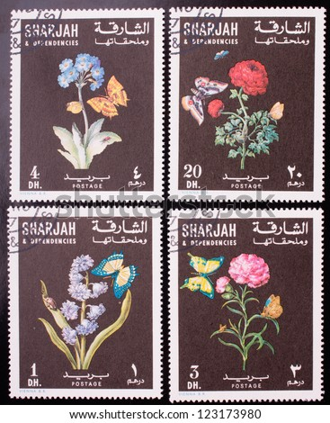 SHARJAH - CIRCA 1967: A stamp printed in Sharjah shows four kinds of colorful flowers and butterflies, circa 1967. - stock photo