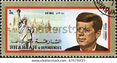 SHARJAH - CIRCA 1973: A stamp printed in Sharjan  shows 35th president of USA John Fitzgerald Kennedy against statue of Liberty in NY, circa 1973 - stock photo