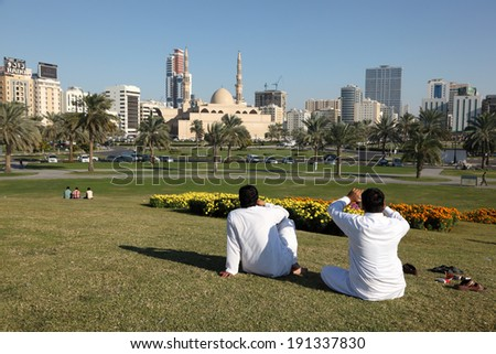 SHARJAH, UAE - DEC 27: Expats Relaxing at the Main Square in Sharjah city. December 27, 2013 in Sharjah, United Arab Emirates - stock photo