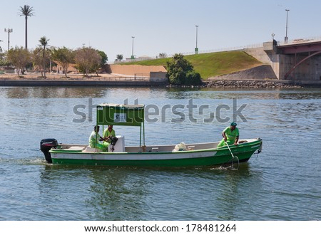 SHARJAH, UAE - OCTOBER 28, 2013: Workers in uniform on the boat cleaning bay.