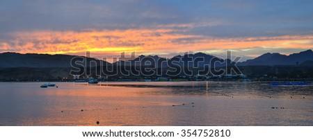 SHARM EL SHEIKH, EGYPT - MARCH 1, 2014: Motor boats anchored among the Bay, evening sunset, red sea coast from the hotel beach Albatros resort, Sharm El Sheikh, Egypt - stock photo