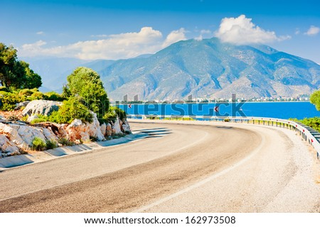 sharp bend in the road and the view of the mountain - stock photo