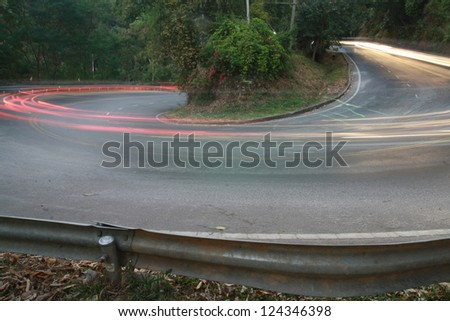 sharp curve road with car light line - stock photo