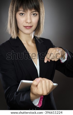 sharp looking business woman using a tablet computer shot in the studio low key lighting on a gray background