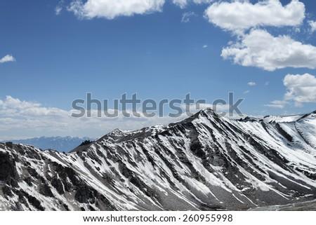 Sharp snow covered mountain ridge - stock photo
