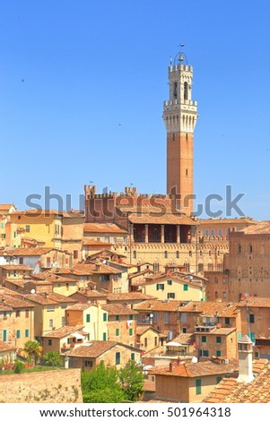 Sharp spire of Torre del Mangia surrounded by medieval buildings in Siena, region of Tuscany, Italy