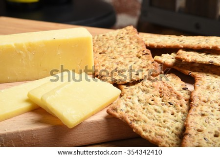 Sharp white cheddar cheese slices with gourmet wheat crackers closeup - stock photo