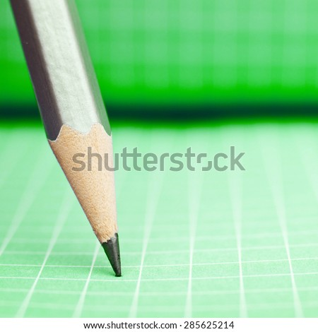 Sharp wooden pencil on green checkered paper - stock photo
