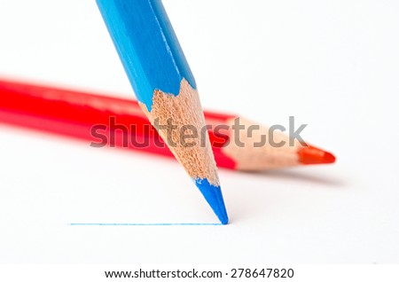 Sharpened blue pencil draws a line on a white paper - stock photo