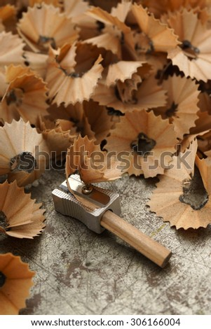 Sharpened pencil, sharpener and wood shavings on aged metal background - close up, macro