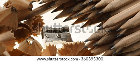 Sharpened pencils, sharpener and wood shavings on isolated on white background  - banner / header edition - stock photo
