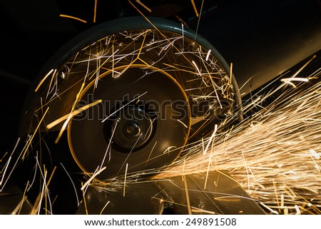 sharpening and cutting of iron by abrasive disk machin - stock photo