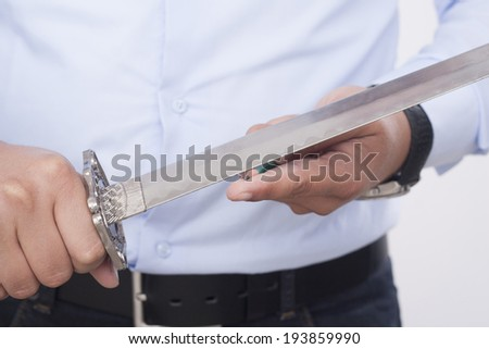 sharpening pencils with a sword...  - stock photo