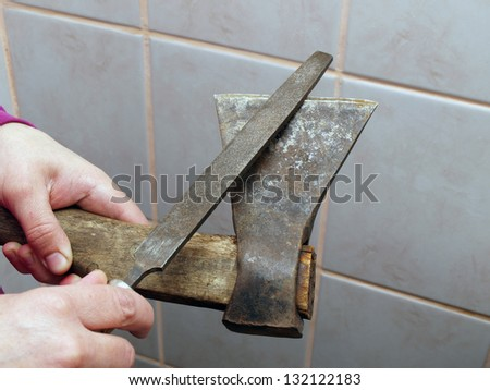Sharpening small axe by file, close up