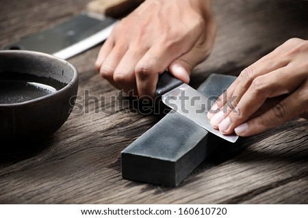 sharpening the knife with whetstone - stock photo
