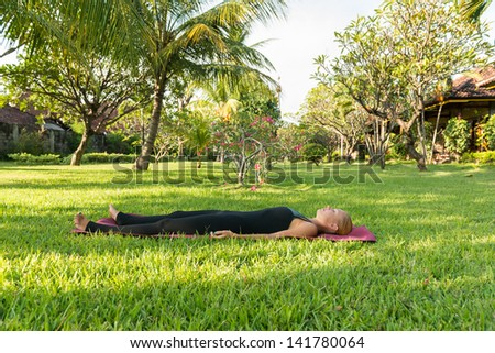 Shavasana. Young woman doing yoga exercises in the lush tropical garden - stock photo