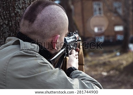 Shaved skinhead is aiming at the window