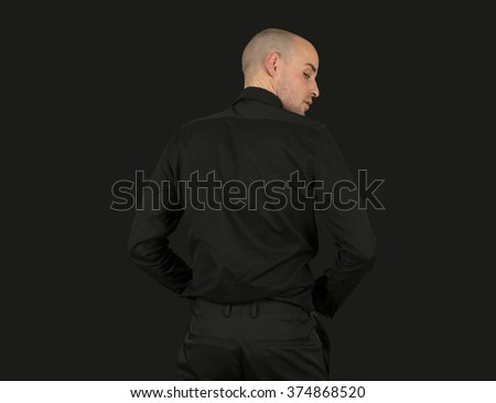 Shaven man wearing a black suit backwards  - stock photo