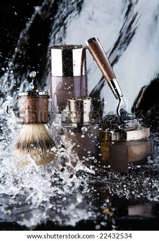 Shaving accessories and water. Close up of male shaving accessories with water background and splashes. - stock photo