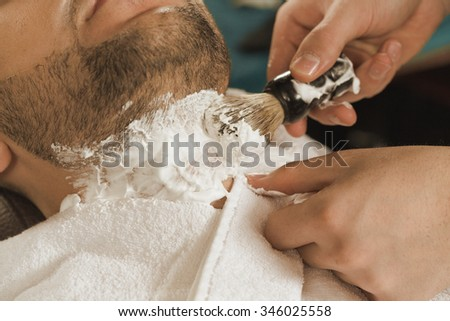 Shaving at barbershop. Closeup shot of a barber applying some shaving cream before shaving neck to his client  - stock photo