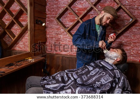 Shaving in the client Barbershop. Berber shaves client - stock photo