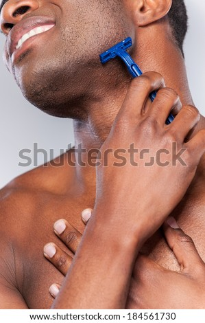 Shaving with wrong razor. Cropped image of young African man shaving and grimacing while standing isolated on grey background - stock photo