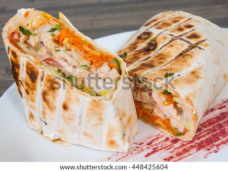 shawarma in thin pita bread with chicken and vegetables on a plate - stock photo