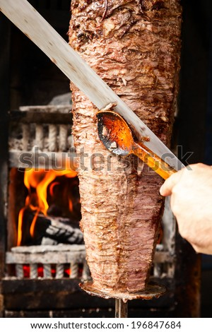 Shawarma meat being cut before making a sandwich - stock photo