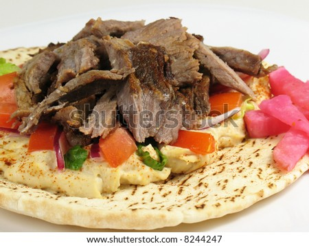Shawarma style beef on a pita, with hummus, lettuce, tomato, red onions, and a side of turnips pickled in beet roots. - stock photo