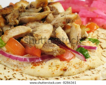 Shawarma style chicken tarna on a pita, with hummus, lettuce, tomato, red onions, and a side of turnips pickled in beet roots.