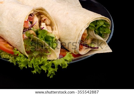 Shawarmas on lettuce on a black background