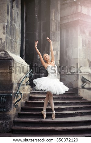 She can teach you grace. Vertical soft focus portrait of a stunning ballet dancer woman performing on the stairway of an old castle  - stock photo