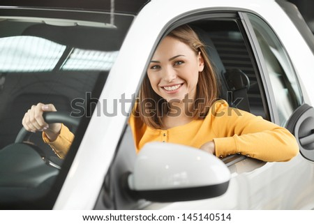 She has bought her dream car! Attractive young woman sitting at the front seat of the car looking at camera - stock photo