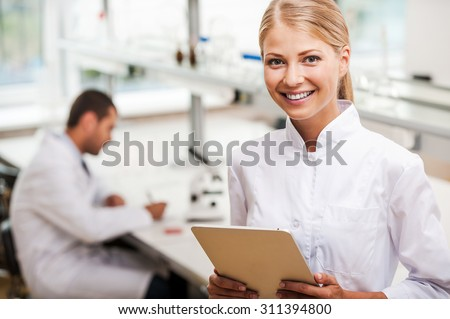 She has brilliant scientific mind. Cheerful young female scientist holding digital tablet and looking at camera while her male colleague working in the background - stock photo