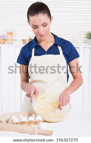 She is a pastry expert. Beautiful young woman mixing dough with wire whisk while standing in a kitchen - stock photo